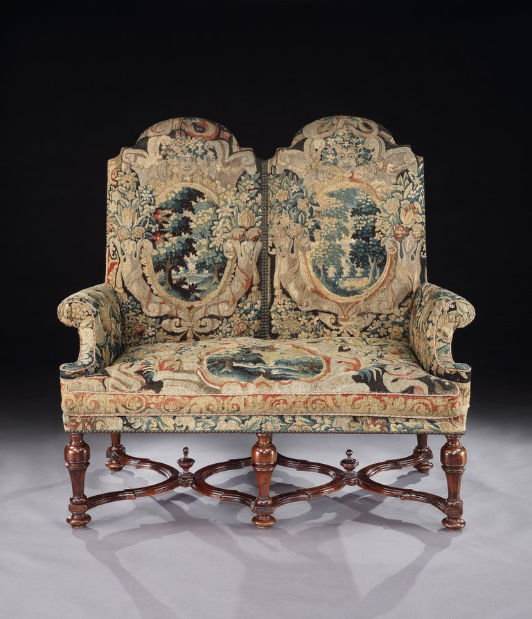 An exceptionally, rare, transitional, double-chair, settee, circa 1700, upholstered in fine, 17th century century Brussels tapestry