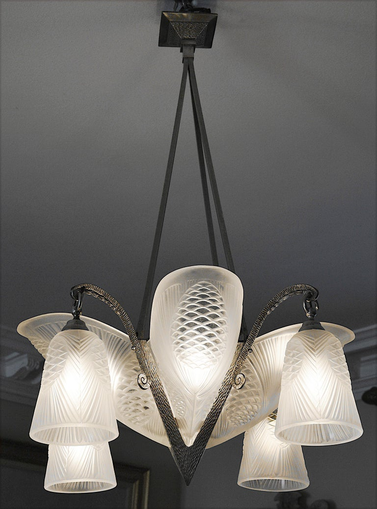 French Art Deco chandelier by Société d'Exploitation des Verreries de Bagneaux, 7 rue de Surène, Paris, France, 1920s. Thick molded glass shades. Original wrought iron fixture. Pine-cone pattern. Same quality as Muller Frères, Degue, etc. Measures:
