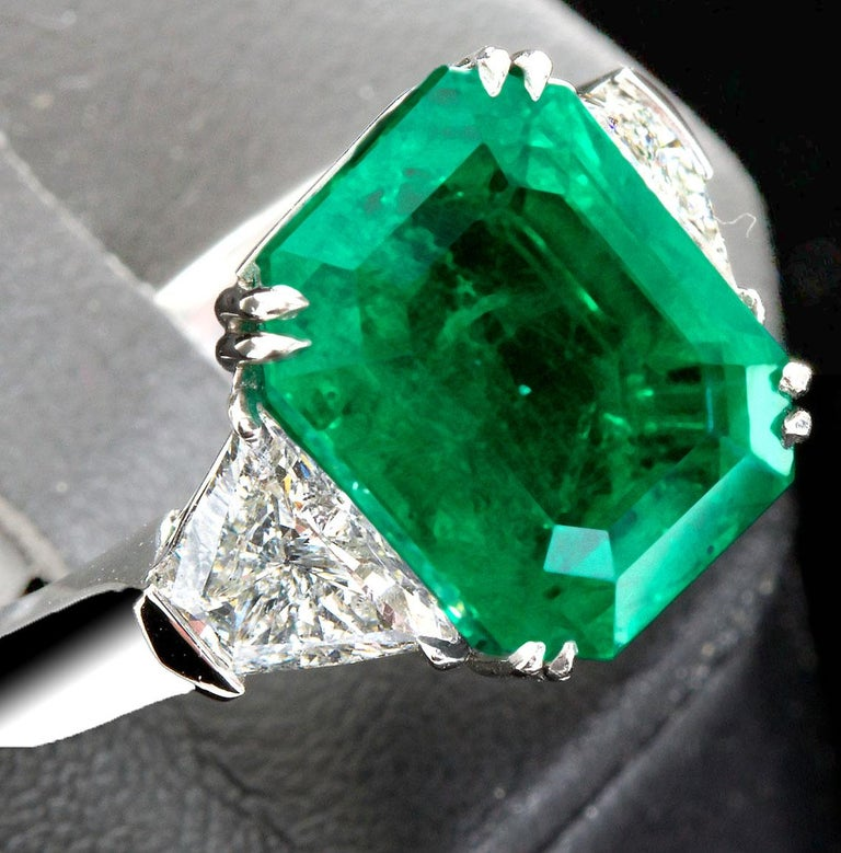 A remarkable deep transparent green 7.44 ct Colombian emerald with only minor clarity enhancement set in a platinum ring with two trapezoid shape diamonds, 1.37 ctw. Accompanied by AGL Prestige Gemstone Report. Emerald size: 13.18 x 10.37 x 6.73