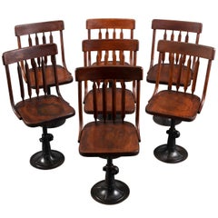 Seven Cast Iron and Wood Adjustable Height Chairs, circa 1895