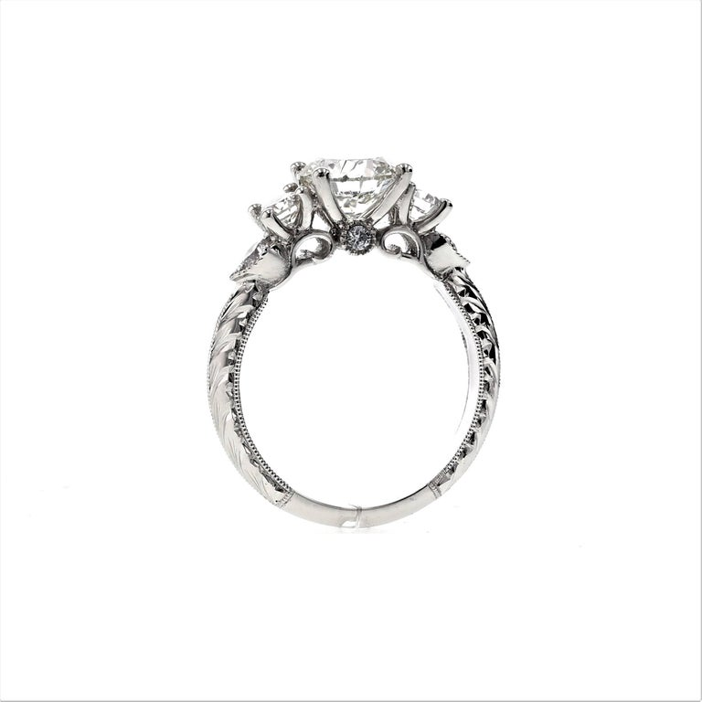This stunning custom engagement ring incorporates seven diamonds and an intricate setting in platinum. Using embellishments such as engraving, bezels and a knife edge, this ring is a masterpiece and timeless in its beauty. It's one of our favorites.