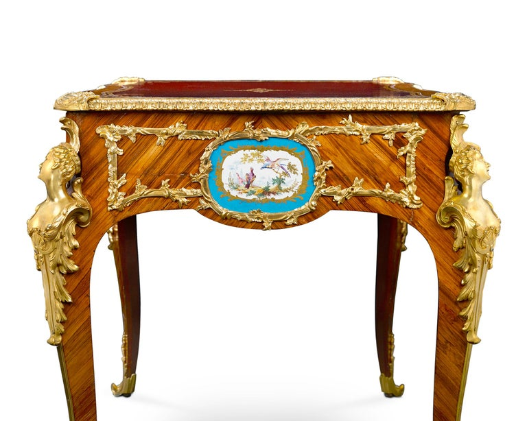 Form and function converge in this exceptional Louis XV-style bureau plat graced with eight elegant Sèvres Porcelain plaques. Framing these delightful, hand painted floral and fowl-themed plaques is a network of exquisite gilt bronze. Supporting the