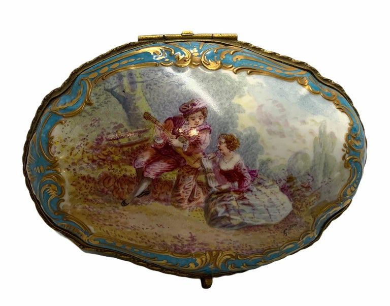 This a porcelain trinket box hinged lid depicting a hand painted 18th century pastoral scene of a young boy learning to play a guitar while his teacher is teaching him the musical notes. The scene is framed with gilt scrolls over a turquoise