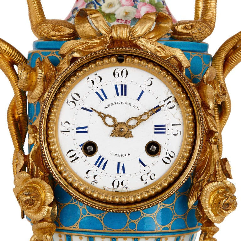 This gilt bronze mounted mantel clock is formed about a beautiful sky-blue, parcel gilt Sèvres style porcelain vase. The enamel dial is mounted within a gilt bronze drum that is draped with gilt bronze garlands and bows. The dial is enumerated with