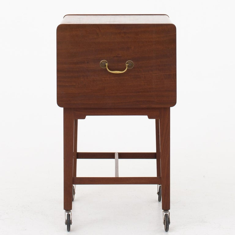 Sewing table in mahogany with brass wheels and handles. Maker Ludvig Pontoppidan.