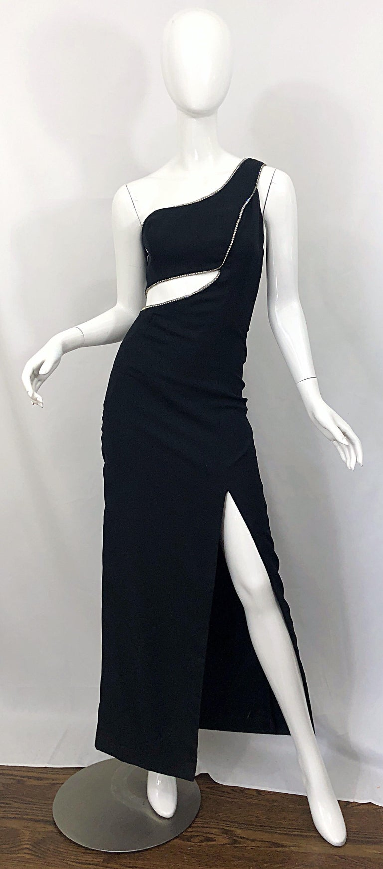 Sexy 1990s black crepe rayon and rhinestone encrusted one shoulder cut-out Grecian evening gown! Very flattering, and super slimming! Features a fitted one shoulder bodice, with cut-outs above the front and back waist. Hundreds of sparkly