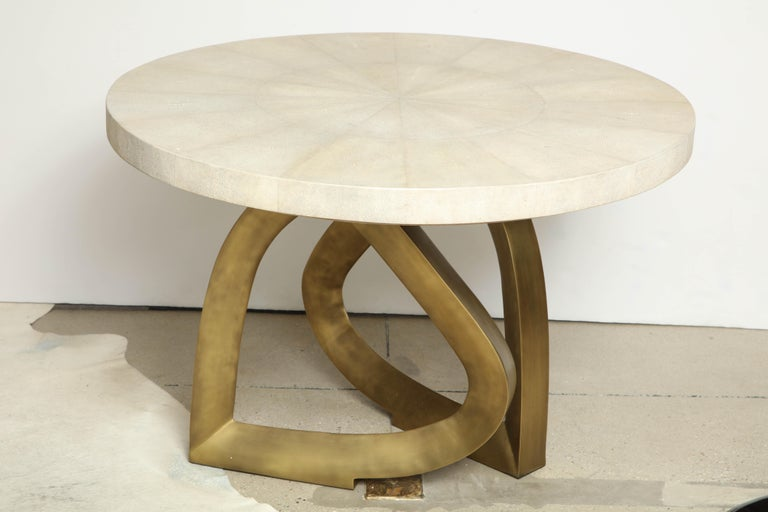 Decorative shagreen cream dining table with an organic shaped brass base, designed in France. We have this table in stock. The top is beautifully made of shagreen. The organic shaped brass base looks like two hearts laid on edge.