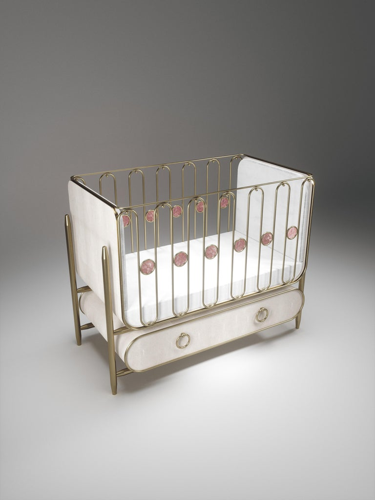 The Riviera Baby Crib by Kifu Paris is the ultimate luxury piece for your child's bedroom. Inspired by the birth of her first child, Kifu Augousti designed this piece to embrace the whimsical world of a child. The piece is inlaid in cream shagreen