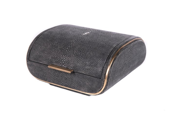The Dandy Box is a chic accent piece for your home. The piece is lined with a removable velvet tray should one wish to use it for jewelry. The piece is completely inlaid in black shagreen, with a discreet bronze-patina brass metal indentation