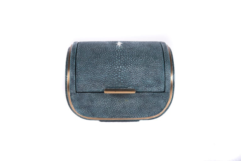 The Dandy box is a chic accent piece for your home. The piece is lined with a removable velvet tray should one wish to use it for jewelry. The piece is completely inlaid in a grey blue shagreen, with a discreet bronze-patina brass metal indentation