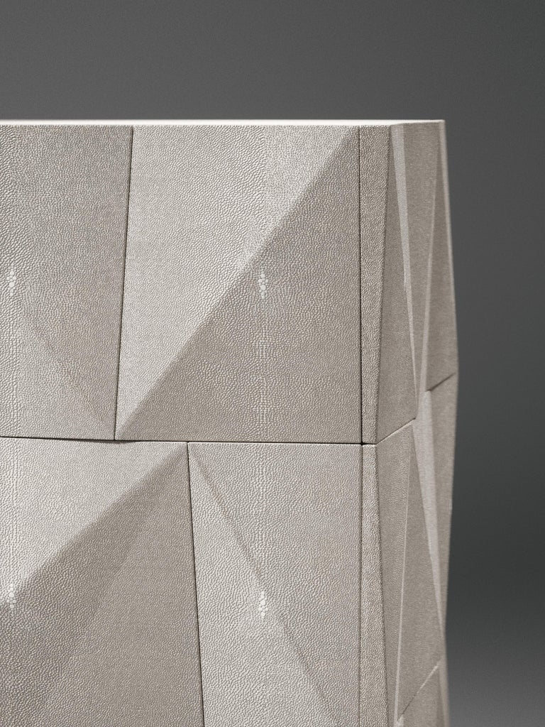 The Rhomboidbedside table by R&Y Augousti is an elegant piece with its fun geometry. This bedside table is completely inlaid in cream shagreen and sits on the option of discreet cut-out bronze-patina brass or solid bronze-patina brass legs. This