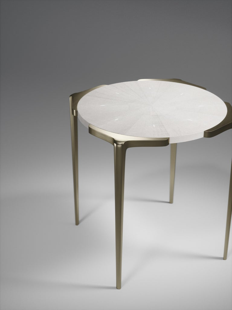 The Eclipse side table inlaid in cream shagreen is an elegant and versatile piece for your home. The top is framed with four bronze-patina brass structures that protrude slightly to create a geometric element to the piece. 
