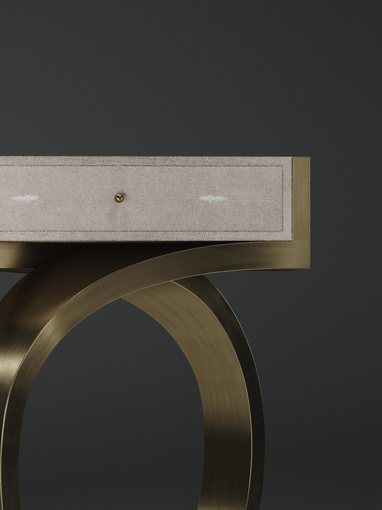 The Ring side table by R&Y Augousti inlaid in cream shagreen is an elegant and sculptural piece for your home. The rectangle top has one drawer with a discreet knob, and sits on the jewelry-inspired bronze-patina brass structure. This piece has a
