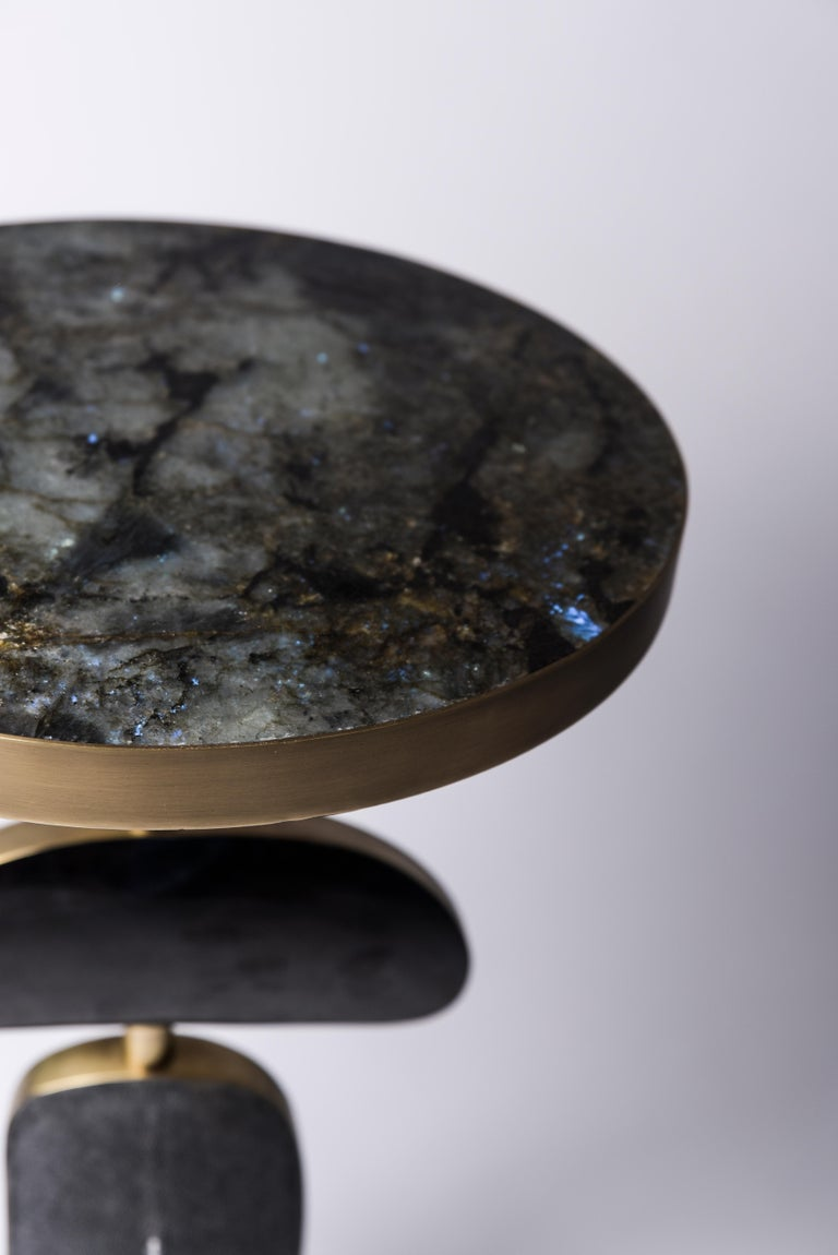 The cosmo side table by Kifu Paris is a whimsical and sculptural piece, inlaid in Lemurian, black pen shell and 2 shades of shagreen: denim blue and black. The amorphous shapes on the bottom part can be moved to adjust the angle of each part.