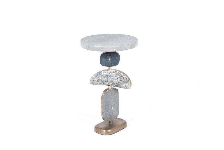 The cosmo side table by Kifu Paris is a whimsical and sculptural piece, inlaid in different shades of blue Shagreen, Baguio stone and bronze-patina brass. The amorphous shapes on the bottom part can be moved to adjust the angle of each part.