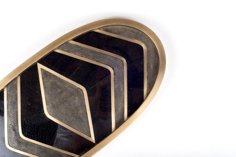 A classic oval vanity tray revisited; this Kifu Paris zig-zag pattern tray is inlaid in a mixture of black shagreen, black shell and bronze-patina brass, making for a stunning tabletop piece in any space. The frame is inlaid in bronze-patina brass.