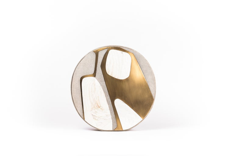 The Cosmos circular vase is a graphic piece that adds a statement to any space. The bold pattern is inlaid in a mixture of mother of peal shell, cream shagreen and bronze-patina brass. The circular vase has a metal indentation around it and is lined