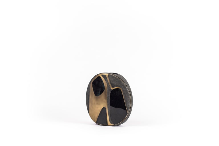 The Cosmos circular vase is a graphic piece that adds a statement to any space. The bold pattern is inlaid in a mixture of black shagreen, blue pen shell and bronze-patina brass. The circular vase has a metal indentation around it and is lined with