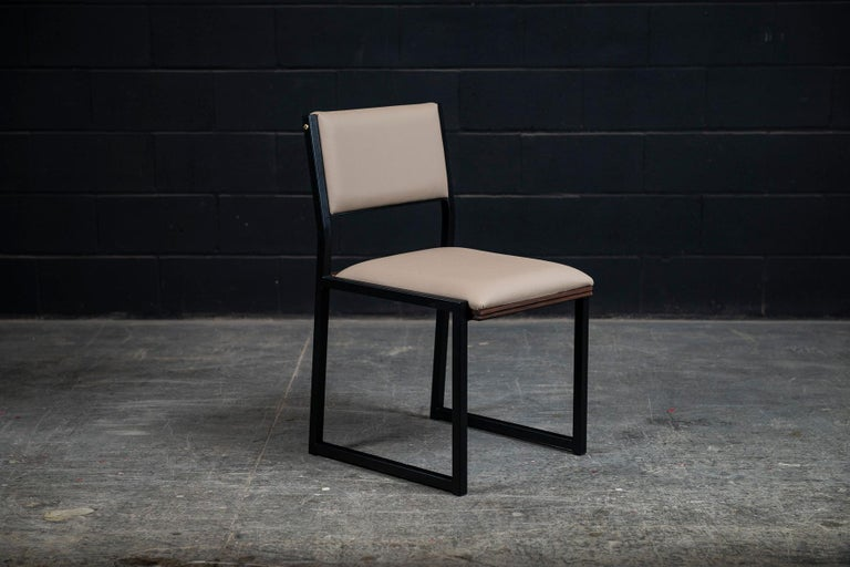 The Shaker modern dining chair is handmade to order from our unique Ambrozia black textured steel tubing frame. Available in a large variety of premium vinyls colors or leather in options. Also offered in COM or COL. Featuring subtitle solid wood