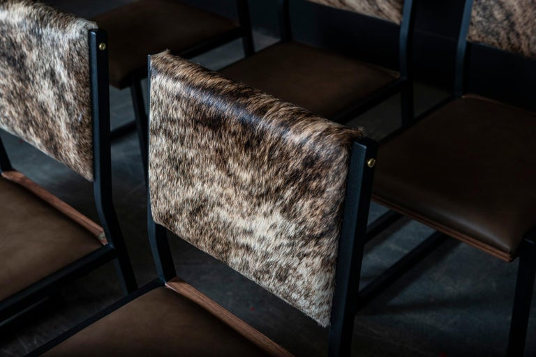 The shaker chair is handcrafted to order from our unique Ambrozia black textured steel tubing frame with a genuine leather seat and Cowhide back. Featuring subtile solid wood insertion that will give a warm and distinguished touch to your space.