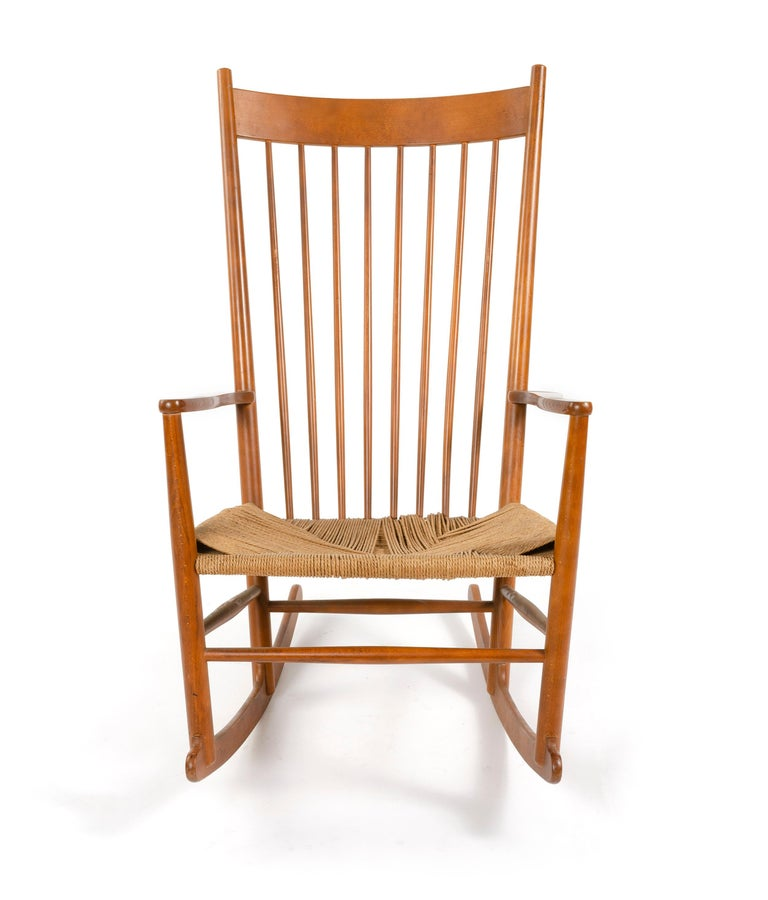 A Shaker Style Scandinavian Modern rocking chair designed by Hans Wegner in beech wood with a woven paper cord seat.