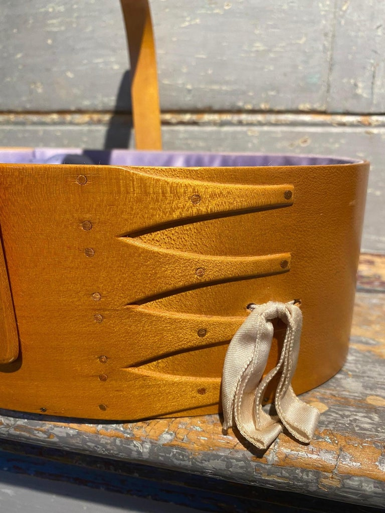 Early 20th Century Shaker Sewing Basket from the Sabbathday Lake Shaker Village in New Gloucester, Maine. An early oval band box made from split poplar with four finger laps and copper rivet fastenings, swing handle and original silk liner and