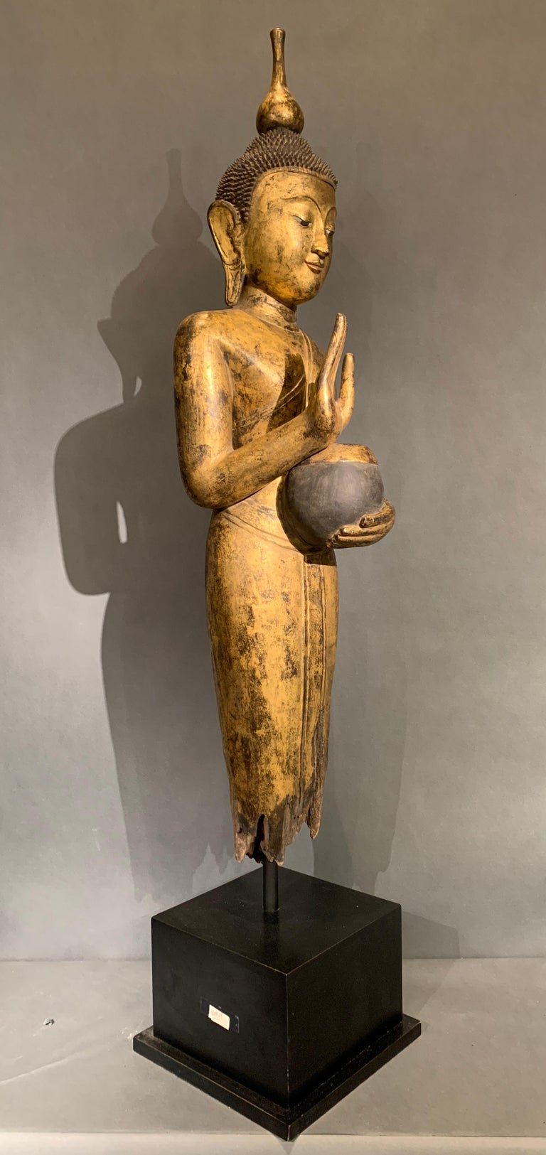 A powerful Shan Burmese standing Buddha of carved and gilt teak wood with shell inlaid eyes, early 20th century.  The Buddha stands upright, dressed in a form fitting monastic robe tied at the waist, one shoulder exposed, with a sash thrown across