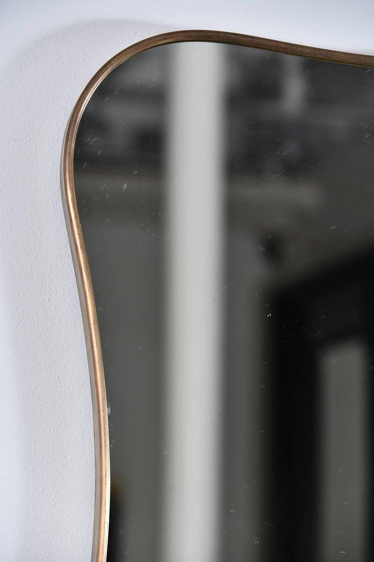 Beautiful curvy, 1950s thin frame brass mirror.