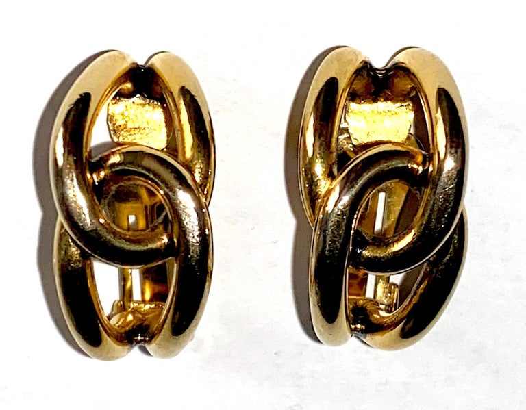 An elegant pair of hoop earrings designed by fashion jewelry designer Sharra Pagano of Milan, Italy. The gold plate hoops consist of two looped round wires that interlock in the center and taper at the ends. Each of the clip earrings measure .63 of