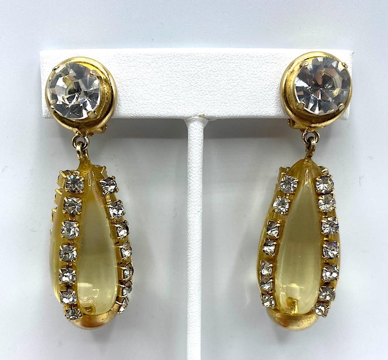 A lovely pair of Italian gold, rhinestone and lucite earrings by Italian fashion jewelry house Sharra Pagano. Each earring is gold plate and clip back. The top pieces has a single large rhinestone mounted in a round button setting .5 of an inch in