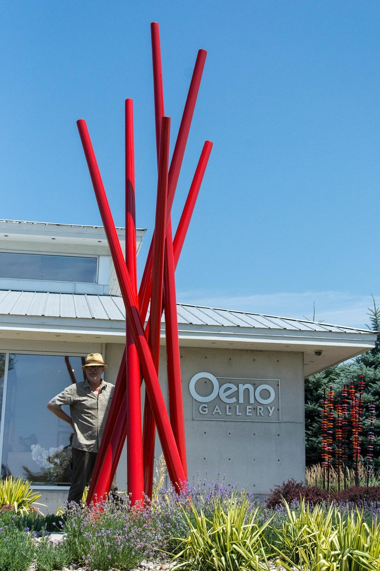 Six tapered steel verticals in poppy red intersect in this soaring outdoor sculpture by Shayne Dark. The dynamic composition may bring to mind sailing masts, sailboats in a harbour.   Poised between abstraction and representation, the artworks of