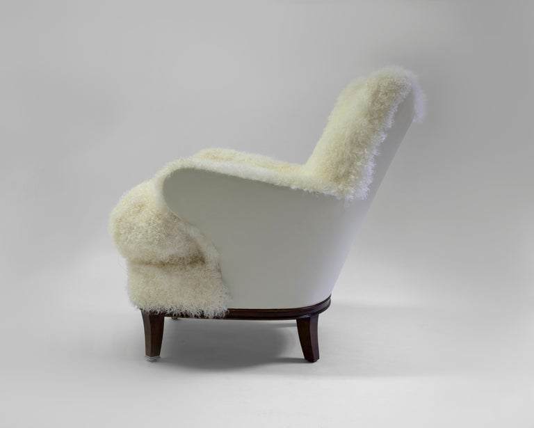 The Willow club chair is a whimsical chair that can be used in any room - shown covered in shearling with button detail on inside back with a contrast leather on the outside back and arms - soft foam with feather and down fill in loose seat cushion