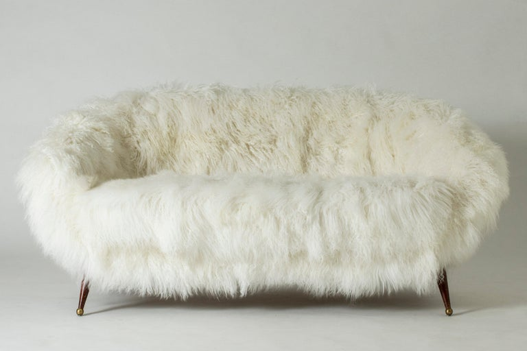 """Stunning """"Tellus"""" sofa by Folke Jansson, upholstered with white, Tibetan sheepskin. Rounded, wide and low design with slender legs with brass balls as feet."""