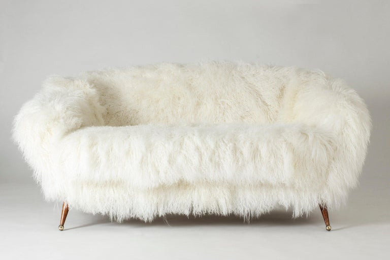 "Stunning ""Tellus"" sofa by Folke Jansson, upholstered with white, Tibetan sheepskin. Rounded, wide and low design with slender legs with brass balls as feet."
