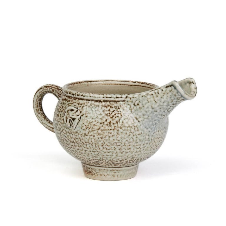 A stunning vintage British Studio Pottery dish by renowned potter Sheila Casson and made in Ross-on-Wye. This stylish rounded bulbous stoneware jug stands on a narrow rounded foot with loop handle and with a raised deep channeled pouring spout. The