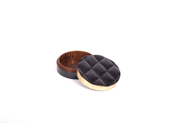 The Coco box is a sophisticated and luxurious accent piece with it's exquisite quilted details. The exterior is inlaid in black pen shell with a bronze-patina brass frame and the interior is inlaid in gemelina wood. This listing is for the medium