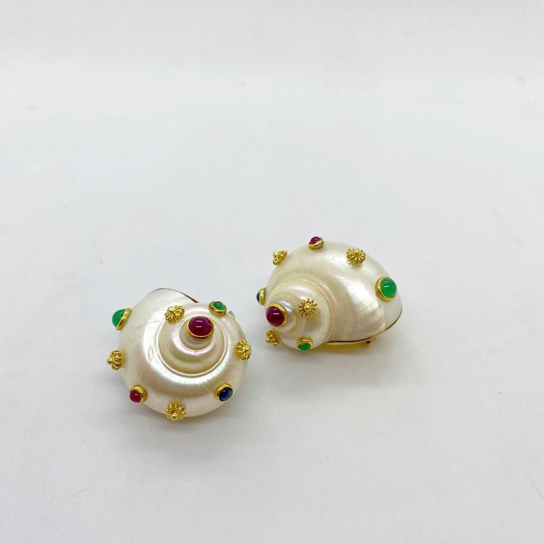 These 18 karat yellow gold earrings are designed with mountings that have been set with shells. The shells are decorated with bezel set Rubies, Emeralds, and Sapphires, along with small gold flowers. The earrings have Omega backs, but posts can be