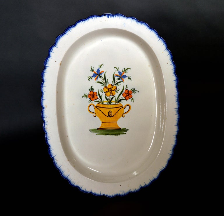 Shell-edge prattware oval dish painted with an urn of flowers, 1800-1820   The oval deep dish has a shaped border in blue with a painted blue shell-edge design. The central well is painted with a large yellow urn with brown details at the border