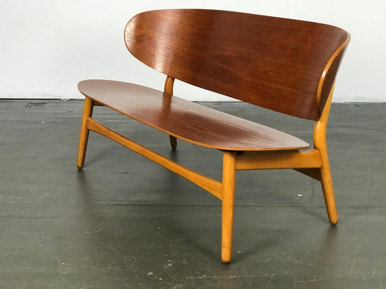 Important settee designed by Hans Wegner for Fritz Hansen in 1948. Made of teak and beech wood, this settee has been restored yet still shows small areas of wear/age. FH stamp underneath.