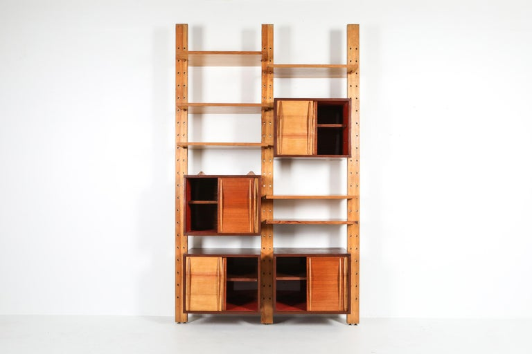 Mid-Century Modern 'bibliotheque', 1970s architect edition, in the style of Charlotte Perriand, Le Corbusier.  The wall unit exists out of 3 poles, 4 cabinets and 6 shelves. two-tone piece in beech and teak.  The system can be expanded with a
