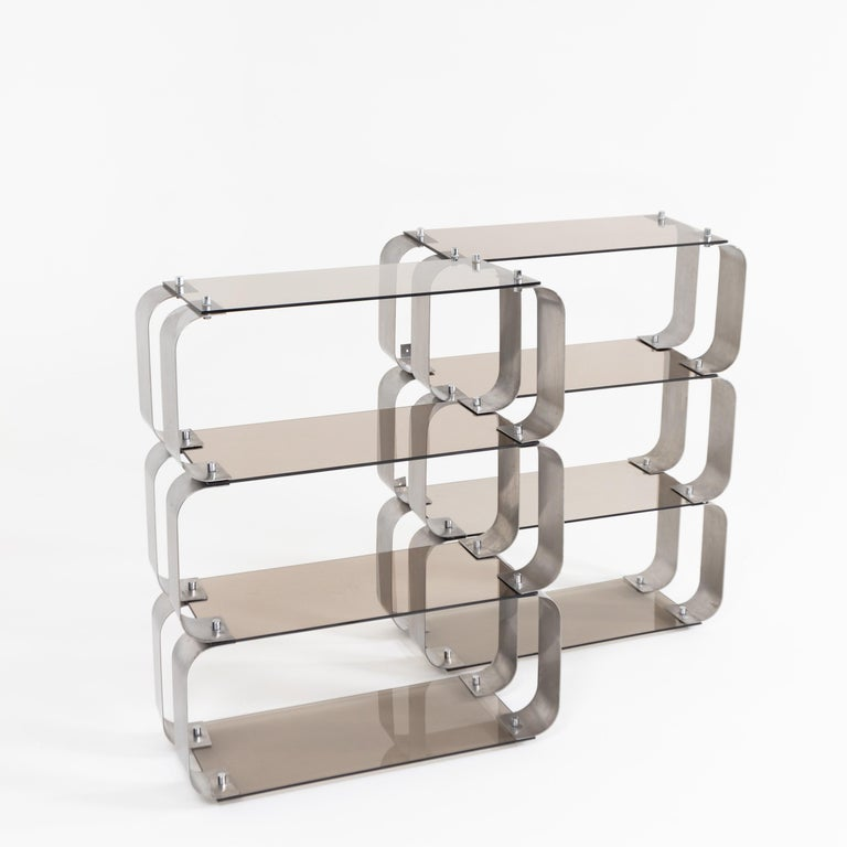 Pair of shelves with c-shaped adjustable steel supports and rectangular smoked glass shelves.