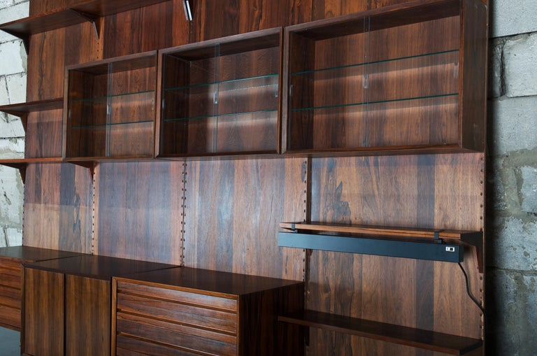 Large wall unit, shelving system by Cado Denmark designed by Poul Cadovius in 1958.  This shelving systems is made in really height quality hard wood. The system allows arranging multiple configurations. Used with some damages scratches on the