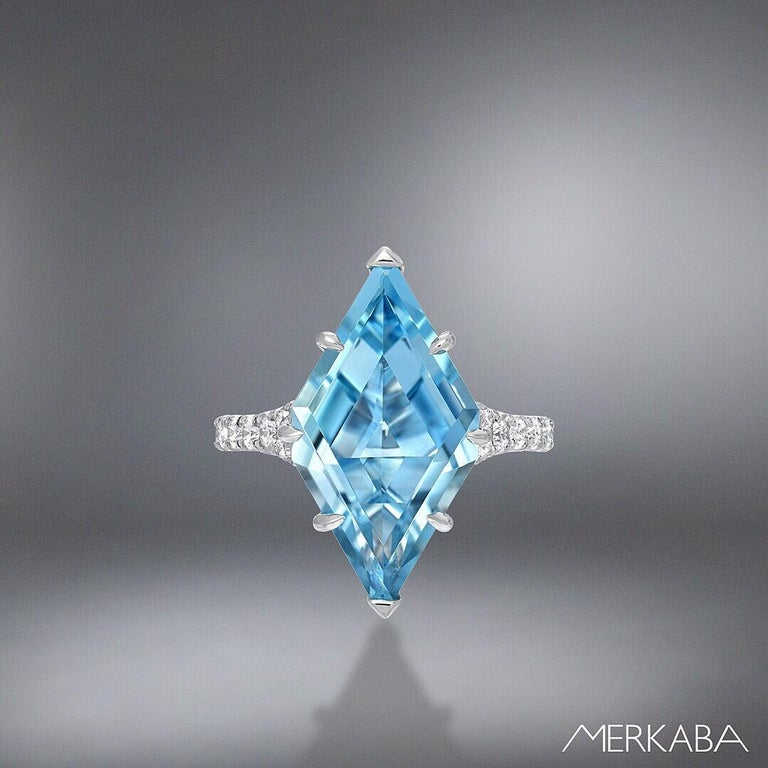 This 4.74 carat custom cut shield Aquamarine ring, is adorned by a total of 0.51 carat diamonds on the split platinum shank. This unique Madagascar Aquamarine is hand set and secured by 6 knife edged, claw shaped prongs.  Size 6. Resizing is