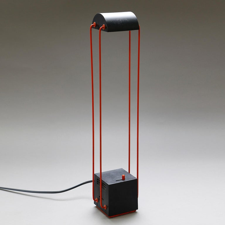 Tokio  A black and red ABS and metal table lamp. The half-cylinder shape reflector on four mobile arms on a cubic base with an integrated dimmer. Original edition by Stilnovo. Italy,  circa 1980.  Note One lamp in the collection of the