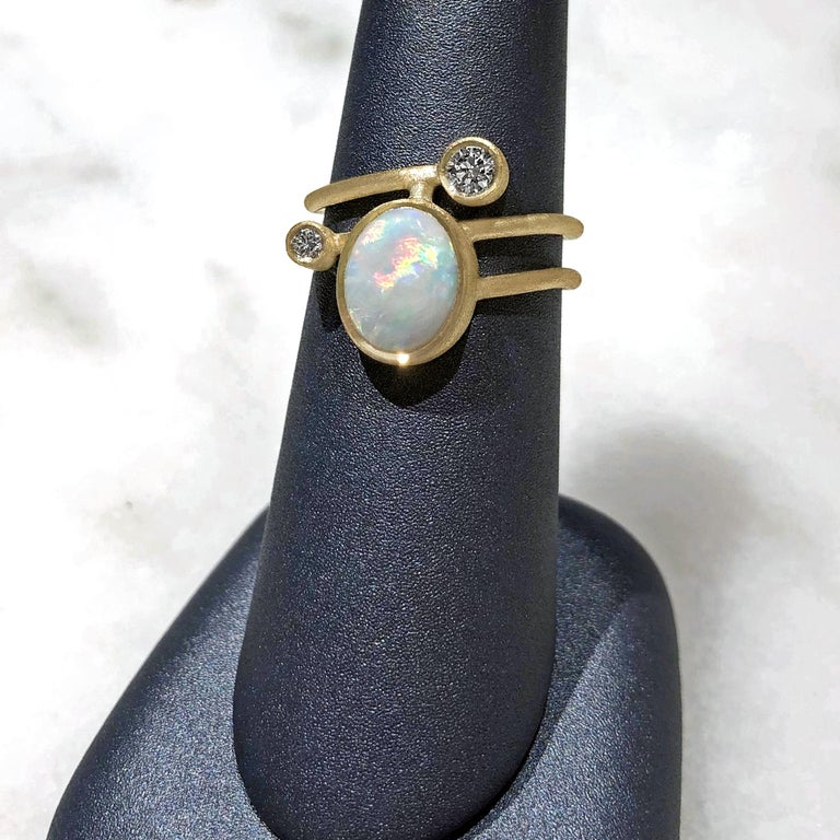 One of a Kind Gamma Ellipse Ring handcrafted in London by jewelry maker Shimell and Madden in beautifully textured 18k yellow gold featuring an oval australian white opal and accented with two round brilliant cut white diamonds totaling 0.22 carats.