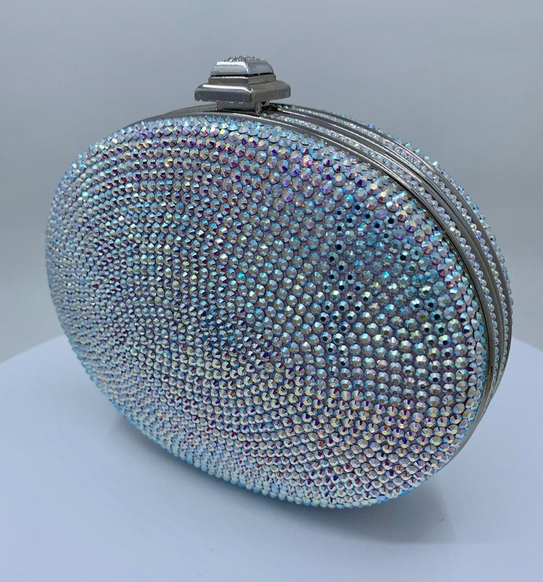Exquisite handmade couture designer, Judith Leiber, shimmering crystal oval shaped minaudiere evening bag or evening clutch is completely covered in a rainbow of opalescent crystals. Silver toned metal frame with metallic silver leather lined