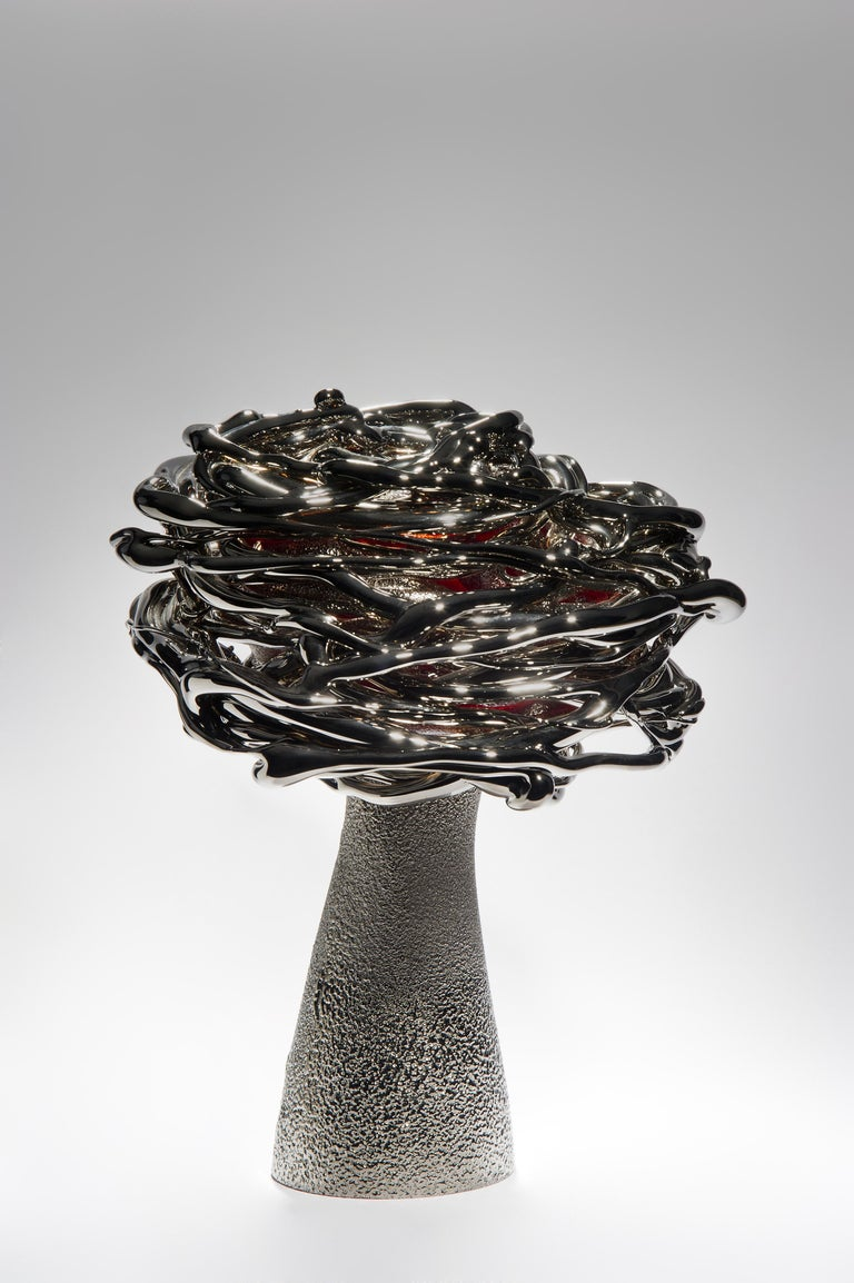 Shining at night, is a unique platinum and glass stylised tree sculpture by the Lithuanian artist Remigijus Kriukas. Glass is blown and hot sculpted to create this substantial artwork, the final piece is finished with a fine coating of
