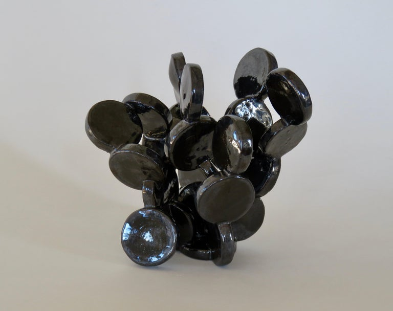 More than 20 small ceramic discs cutout and connected by hand, glaze fired into a unique, shiny black table-top sculpture. Reminiscent of a favorite plant or molecular structure, different from every angle. Fully handmade, no two are ever