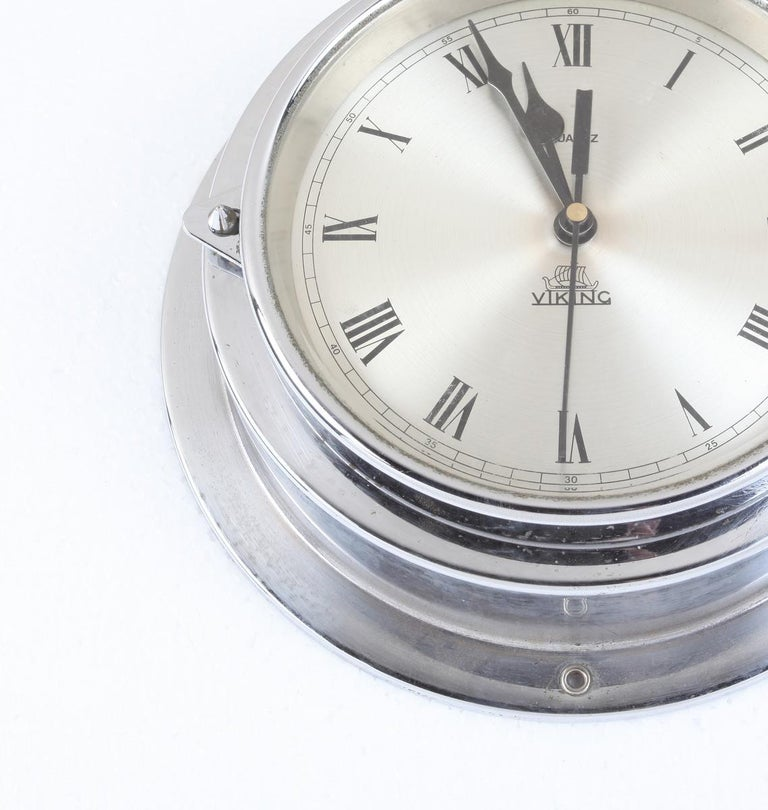 A ship's chrome, battery operated wall clock by Viking. Signed Weilbach & Co., Copenhagen. Battery mechanism replaced putting it in good working order; and piece has been polished up. Roman numeral nickel face which measures 6.25