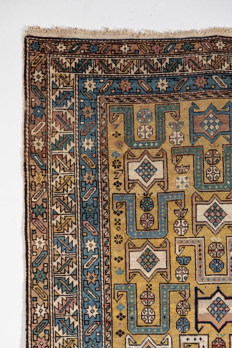 Antique Caucasian rug with unusual color palette. Even pile, ends complete, few small damages as shown. Gold background with geometric and floral motifs. Red, ivory, blue, green, pink, brown, orange.